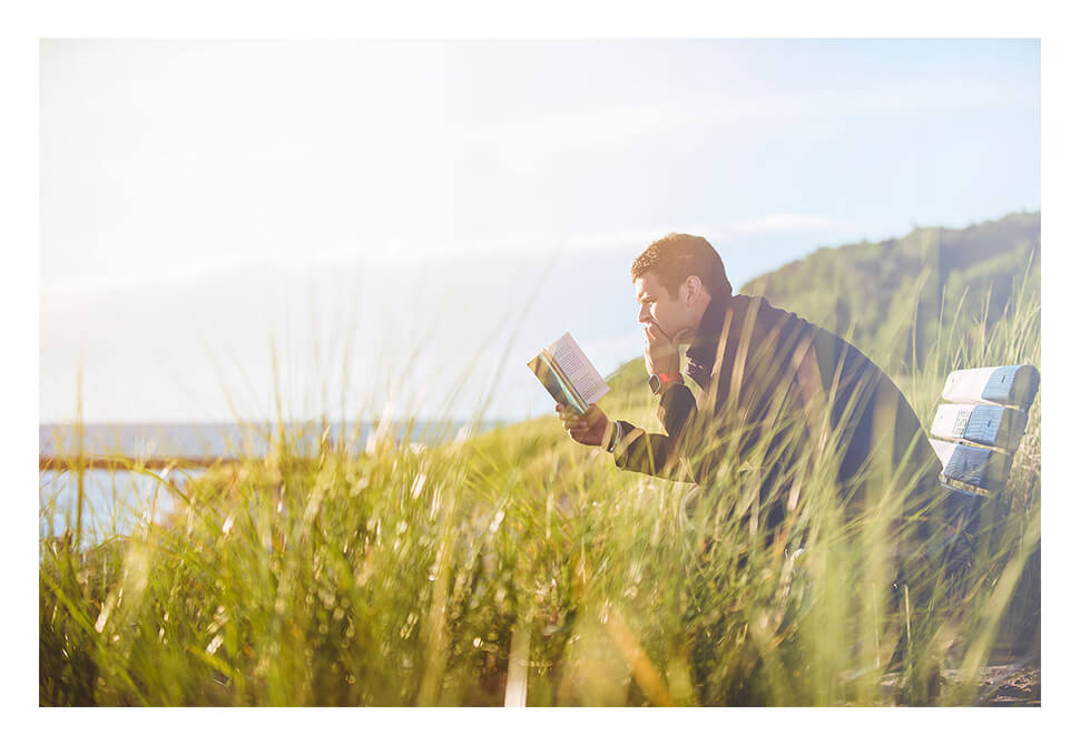 Man leisurely reading outdoors on a park bench