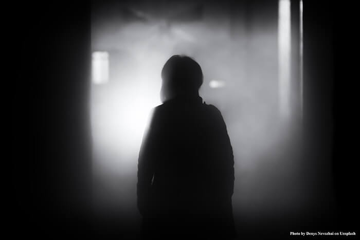 A woman tries to walk through a dark & misty room